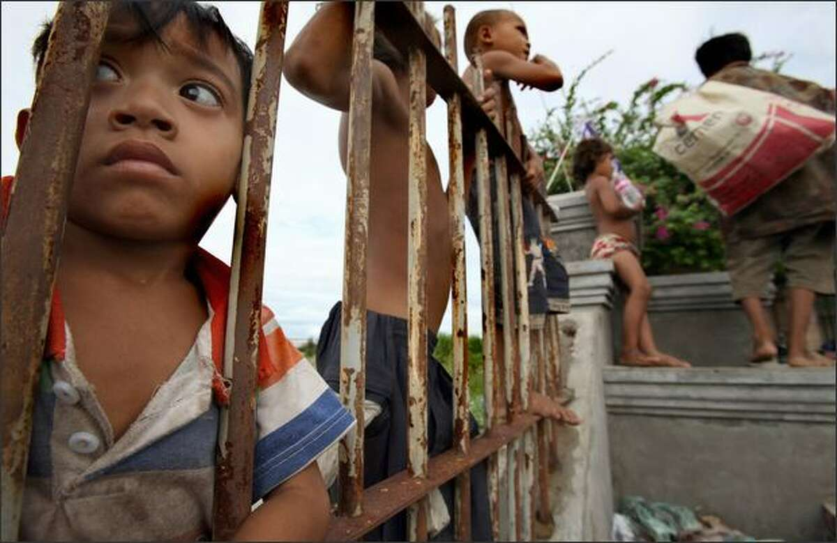 Cambodian scavengers look through and over a fence to watch a ceremony marking World Against Child Labour Day in Phnom Penh. Some 500 Cambodian school children marched to mark the day, calling for parents to send their kids to school rather than forcing them to work.