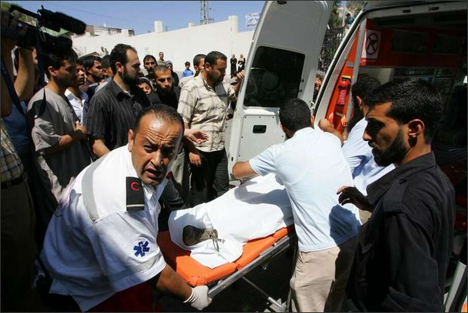 A body of Palestinian is wheeled into an ambulances workers after the car he was in was hit in an Israeli air strike Tuesday in Khan Yunis,in the southern Gaza Strip. According to reports, five Palestinians were killed in the strike. The strike came on the same day that Hamas and Israel agreed to a Egyptian brokered ceasefire that will begin June 19. Photo: Getty Images / Getty Images