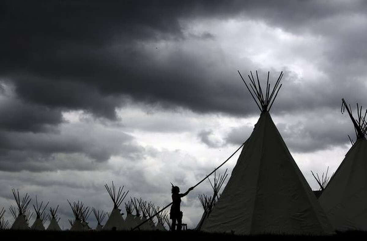 A crew member from Boutique Camping erects a tipi at the Glastonbury Festival site near Glastonbury, Engand. Next week, the tipis, which are fully booked and cost 800 pounds to rent, will be occupied by festival-goers joining more that 170,000 other music fans for what is generally considered Europe's biggest music festival.