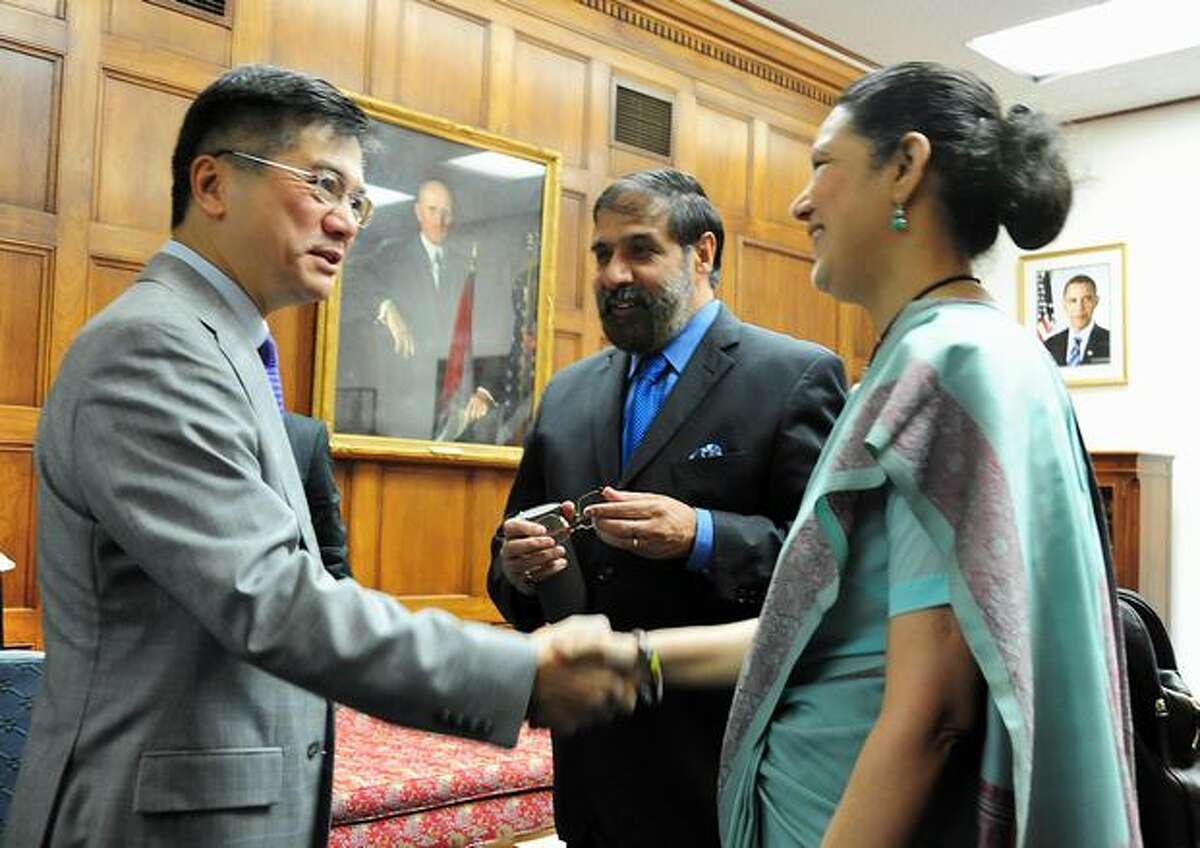 Indian Commerce and Industry Minister Anand Sharma, middle, looks on as U.S. Commerce Secretary Gary Locke, left, shakes hands with Ranendra Sen, India's ambassador to the United States, for a photo opportunity before meetings in Washington, D.C.