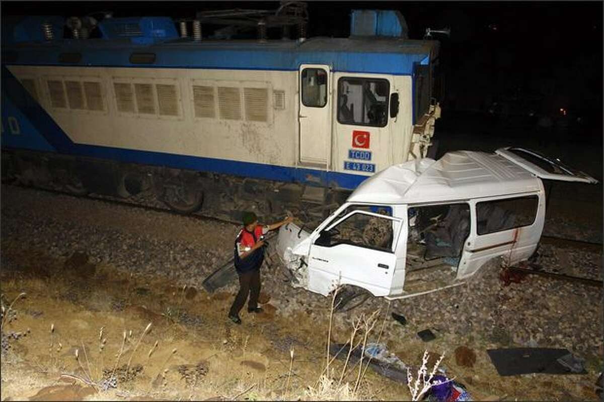 A Turkish police officer stands near the railway accident area in Gaziantep. Eleven people were killed in Turkey when a freight train rammed into a minibus which was passing a level crossing despite warnings to stop, officials said.