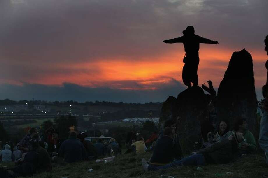 Glastonbury Festival-goers gather at the stone circle to watch the sun rise in Glastonbury, England. The gates have opened for the first of the 140,000 music fans arriving at what has become one of Europe's largest music festivals, but weather forecasters have warned that bad weather may be on the way. Photo: Getty Images / Getty Images