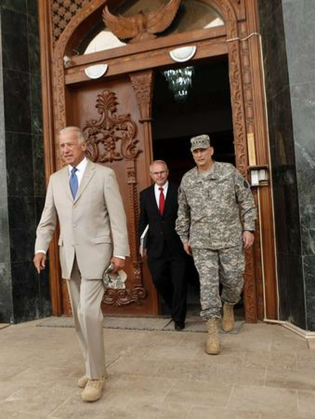 U.S. Vice President Joseph Biden, left, U.S. Ambassador Christopher Hill, center, and Gen. Ray Odierno emerge from a U.S. military base near Baghdad. This is Bidden's first trip to Iraq as vice president and comes days after U.S. forces pulled out from Iraq's cities.
