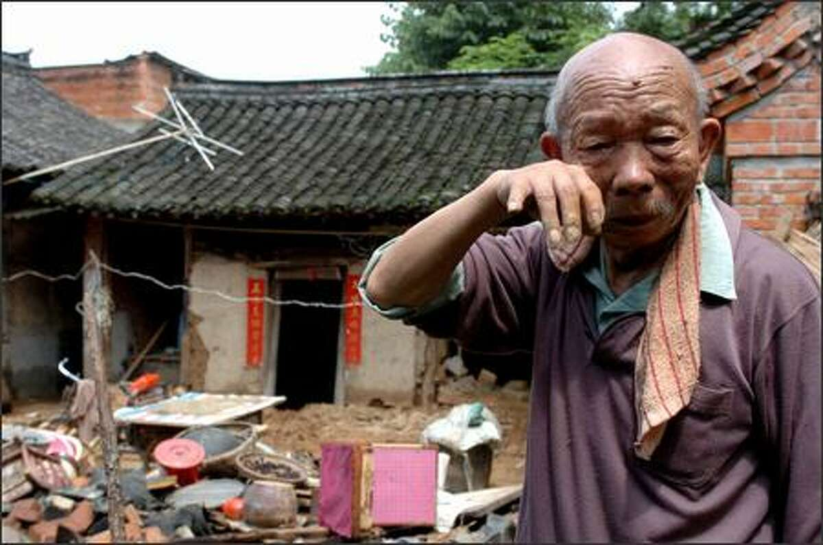 In this photo released by China's Xinhua News Agency, Hua Dinghong, 74, grieves over his house flooded in a storm in Hanzhong of northwest China's Shaanxi Province Friday, July 6, 2007. A week-rain has caused 5 death and 2 people missing in the area, Xinhua said. (AP Photo/Xinhua, Tao Ming)