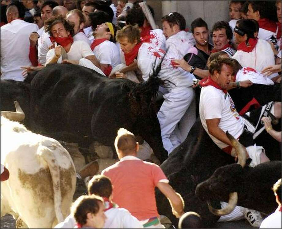 "Participants are charged by Conde de la Corte fighting bulls on the first day of the San Fermin bull run on Monday, in Pamplona, northern Spain. Spain's annual San Fermin is known to many worldwide for the ""encierro"", when bulls are released onto the streets each morning and hundreds of people are chased along an 825-metre course leading to the arenas where bullfights are later staged. - Story: Many injured in 1st day of Spain's running of the bulls Photo: Getty Images / Getty Images"