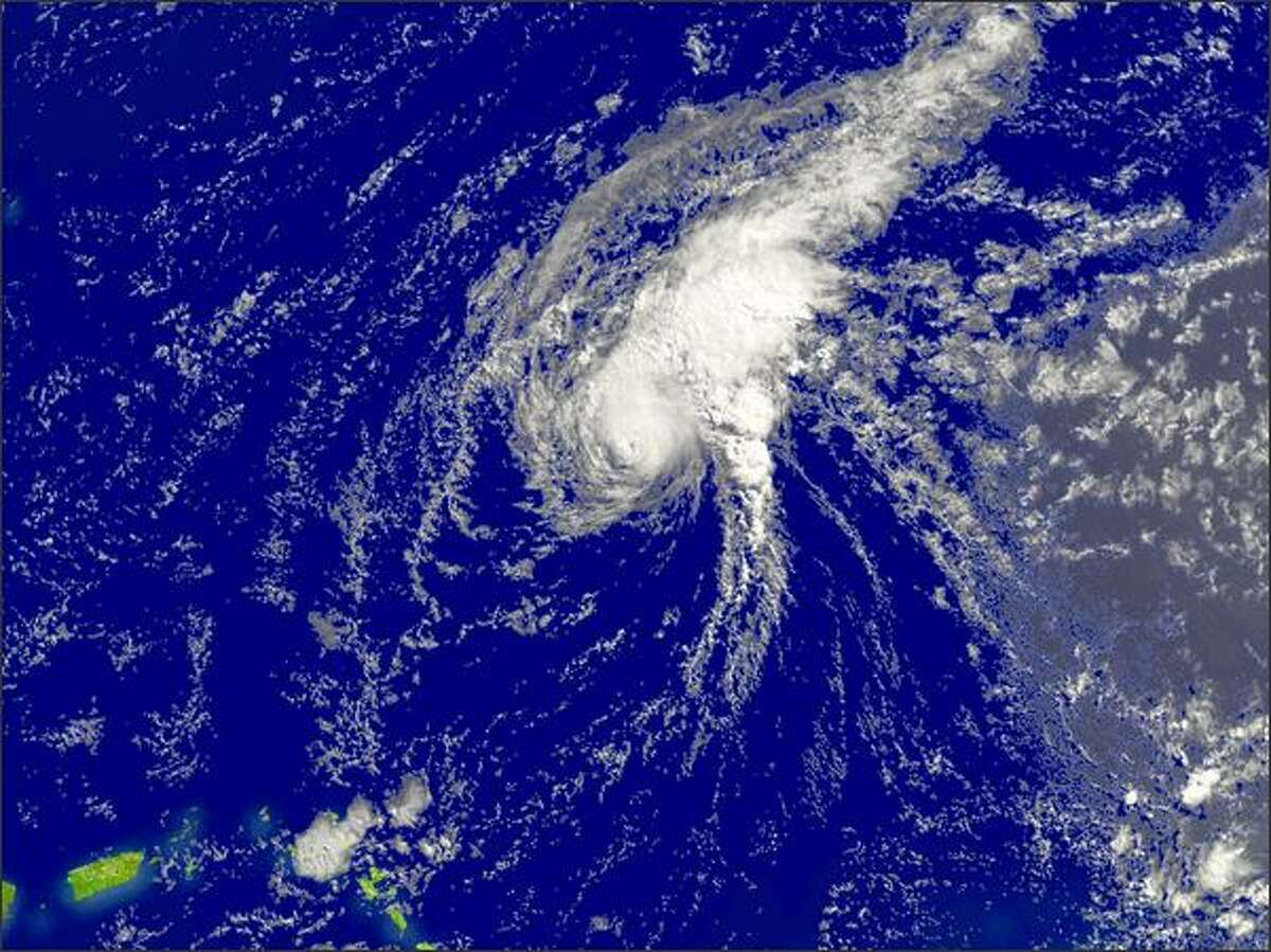 In this satellite handout image provided by the National Oceanic and Atmospheric Administration, Hurricane Bertha continues to gain strength off the southeast coast of Bermuda at 11:45 GMT Tuesday in the Atlantic Ocean. Bertha was named the first hurricane of the Atlantic season when it was upgraded from a tropical storm. Bertha is moving toward the northwest at 10 MPH with maximum sustained winds near 120 MPH.