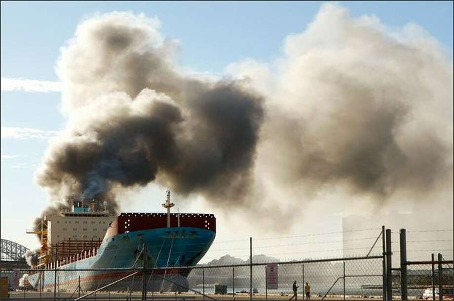 A fire is seen at the White Bay dockyard in Balmain on Wednesday in Sydney, Australia. Machinery inside the floating demountable work shed ignited the blaze onbaord where it was parked behind the 'Maersk Sealand' tanker at 8.30am. Photo: Getty Images / Getty Images