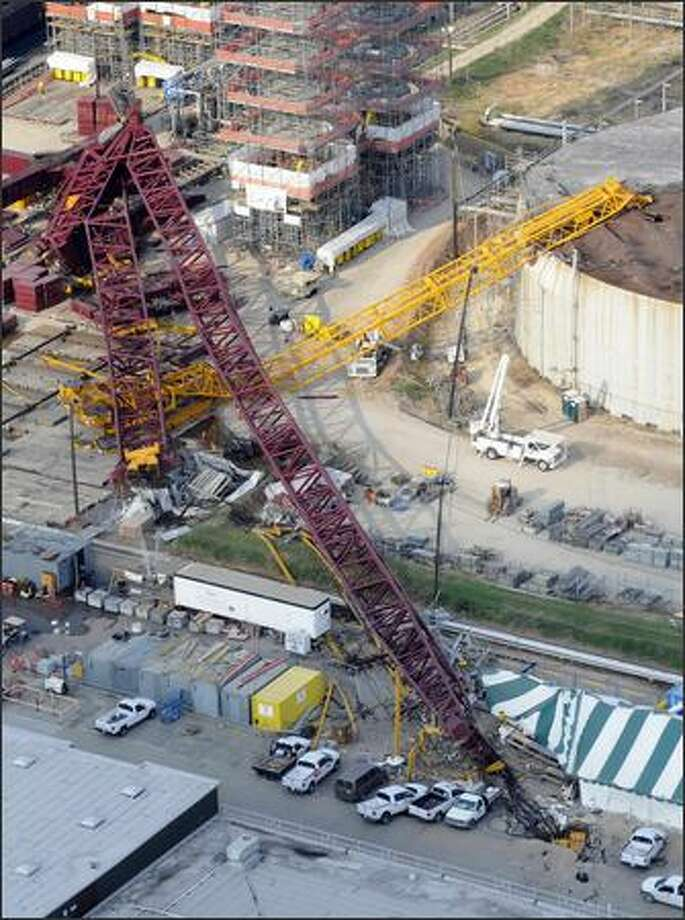 A collapsed crane is visible within the LyondellBasell Houston Refinery, Friday in Houston.. One of the nation's largest mobile cranes collapsed at a Houston oil refinery Friday, killing four workers and injuring seven others in the latest of several fatal accidents that have raised concerns about the safety of construction cranes. (The Houston Chronicle/Steve Ueckert) - Story: Crane collapses at Houston refinery, killing 4