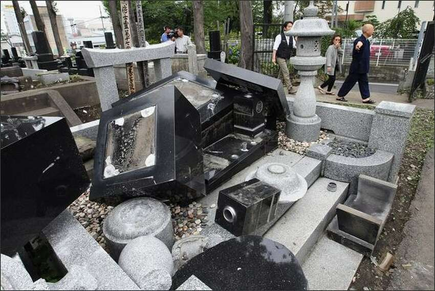 Gravestones are destroyed at Honchuji temple in Hachinohe, Aomori, Japan. More than 100 people were injured by the magnitude 6.8 earthquake.
