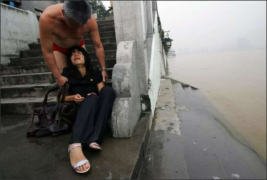 A young woman sits crying as a swimmer calms down her at the shore of the Hanjing River July 25, 2007 in Wuhan of Hubei Province, China. The woman tried to drown herself, but was pulled from the water by two swimmers. About 90 percent of the estimated 30 million people in China suffering from depression fail to get proper treatment due to the stigma and due to a shortage of professional psychiatrists, according to the Chinese Psychiatrist Association. (Photo by China Photos/Getty Images)