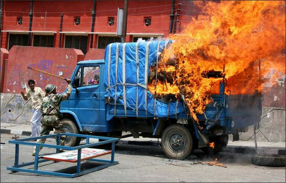 An Indian Central Reserve Police Force policeman attempts to douse a burning police vehicle in Jammu after it was set alight by demonstrators during a protest. The protest was sparked by the reversal of a decision by the government of Indian-administered Kashmir to allocate land to a Hindu trust. On July 11, Kashmir was put under federal rule following the collapse of the state government because of the land row.