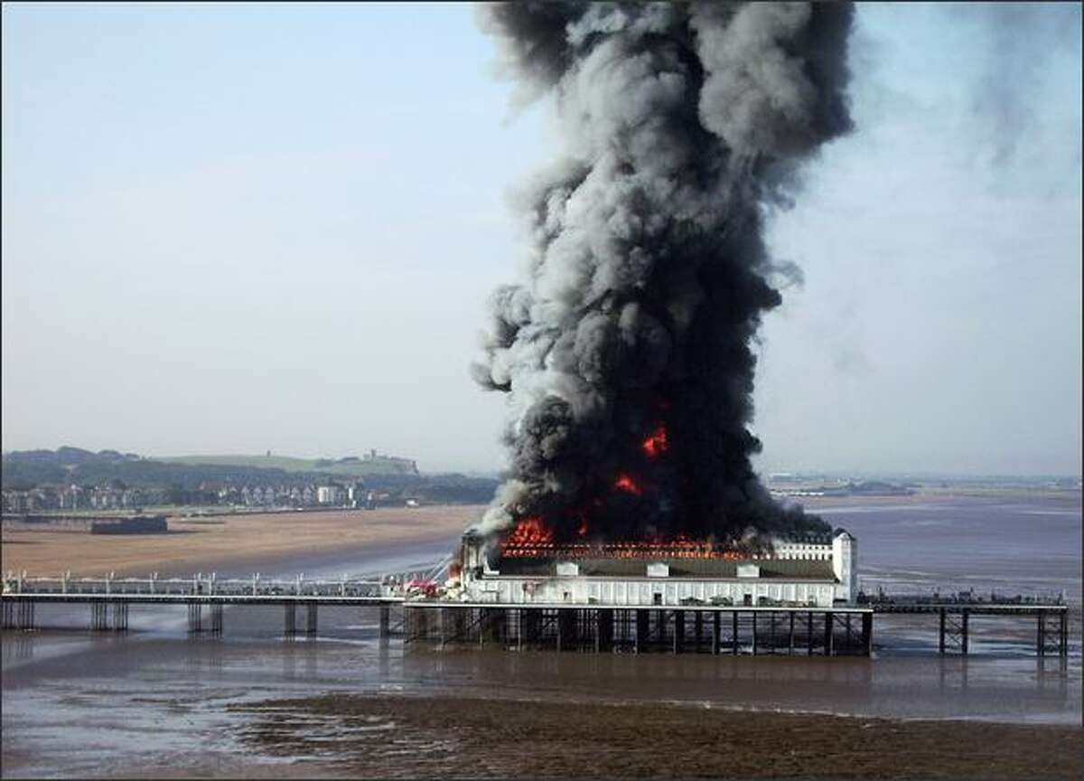 The Grand Pier, one of Britain's biggest, burns in Weston-Super-Mare, England. Firefighters are tackling the huge fire that has engulfed the historic Grand Pier in the seaside resort in Somerset.