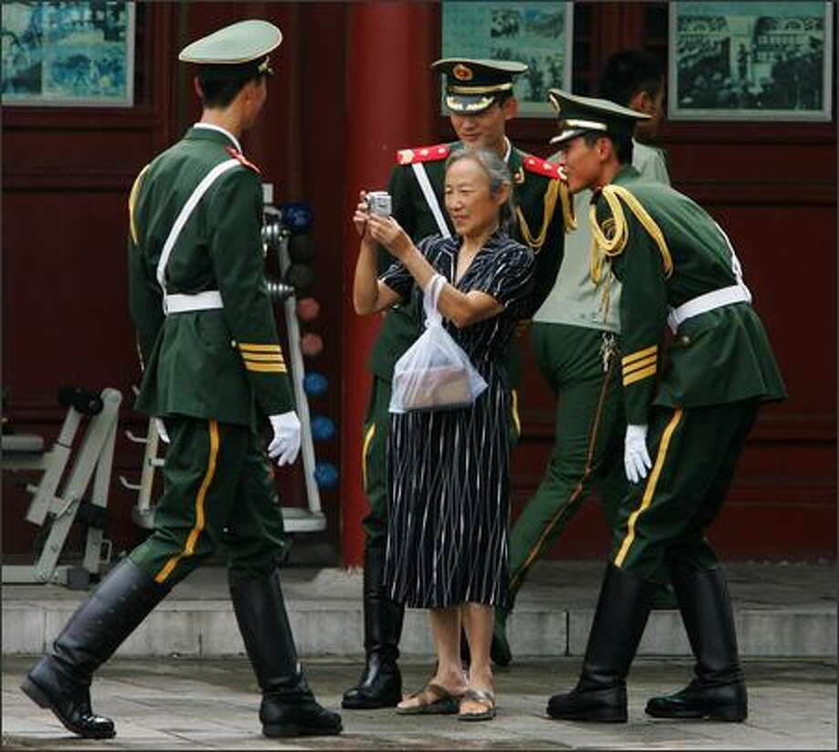 Chinese armed policemen look at their photos on a woman's digital camera during a gift ceremony to mark the 80th anniversary of the founding of the People's Liberation Army (PLA) at their barracks on July 31, 2007 in Beijing, China. The PLA, the world's largest standing army with 2.3 million members, celebrates its 80th anniversary on August 1. Photo by Guang Niu/Getty Images