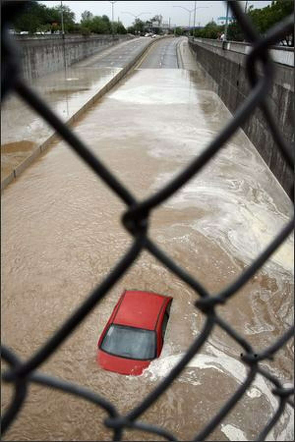 A car is stranded in the west-bound lane of Aviation Parkway is shown Tuesday, July 31, 2007, in Tucson, Ariz. AP Photo/Daily Star, Jeffry Scott