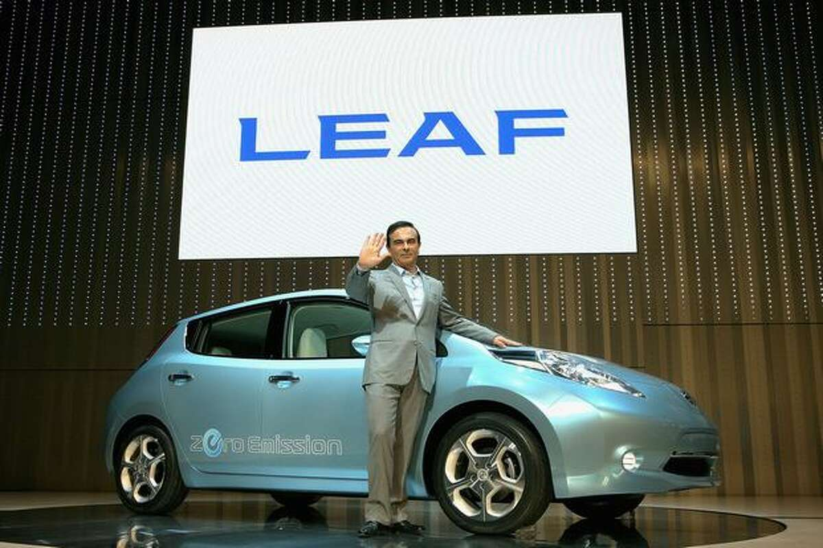 Nissan Motor Co. President and CEO Carlos Ghosn poses with the new Nissan Motor Co.'s zero-emission electronic vehicle (EV) 'Leaf' during the opening ceremony of new Nissan Global Headquaters on Sunday in Yokohama, Kanagawa, Japan. Nissan returns to its birthplace. The electronic vehicle, designed specifically for a lithium-ion battery-powered chassis, will be released in late 2010.