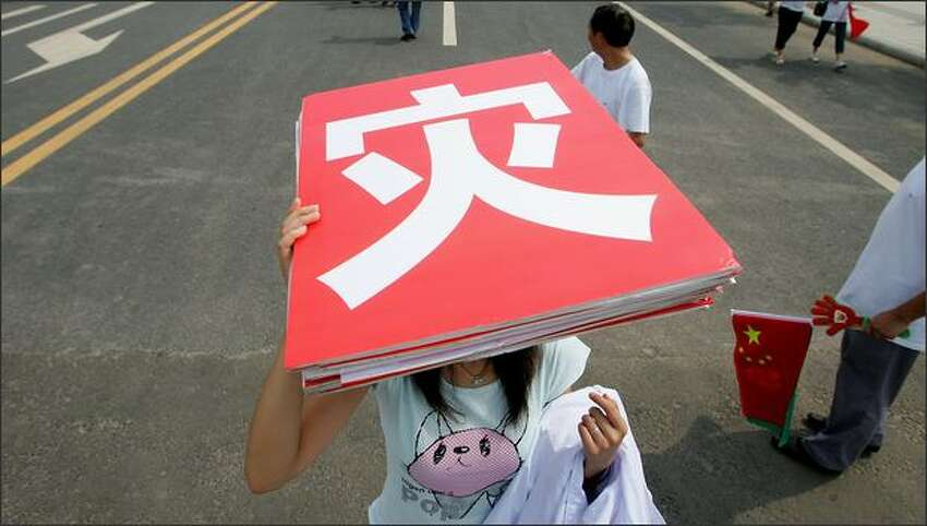 A student carries a sign board reading disaster after she took part in the Mianyang leg of Beijing Olympic torch relay outside the Jiuzhou stadium on Monday in Mianyang of Sichuan Province, China. The three-day Beijing Olympic torch relay held in the quake-hit Sichuan province, the last relay leg before Beijing.