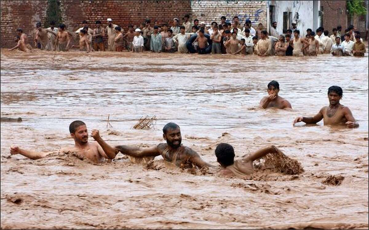 Pakistani volunteers rescue villagers in a flooded area on the outskirts of Peshawar on Monday. At least 20 people have died in flash floods in northwest Pakistan after heavy monsoon rains, officials said.