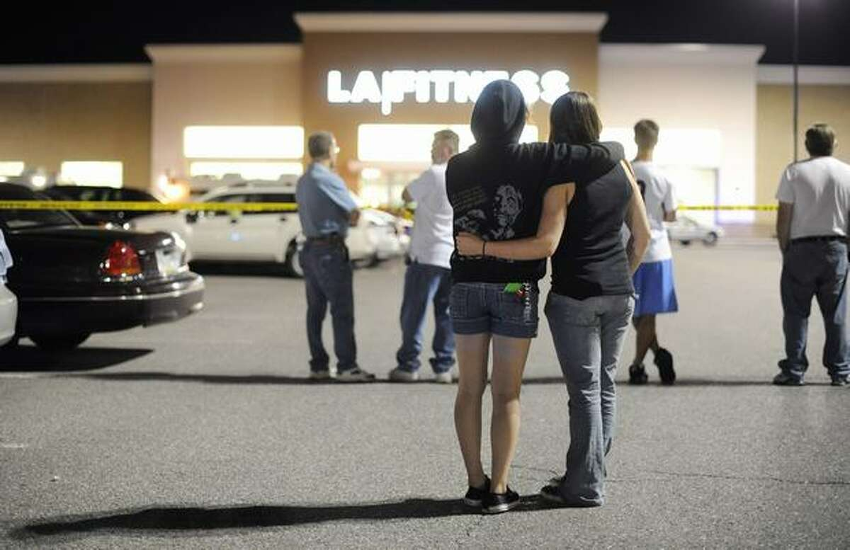 People stand outside a LA Fitness following a shooting inside the health club Tuesday in Bridgeville, Pa. A gunman walked in to an aerobics class in a shopping center in Collier Township, killing at least four people and wounding nearly a dozen others.
