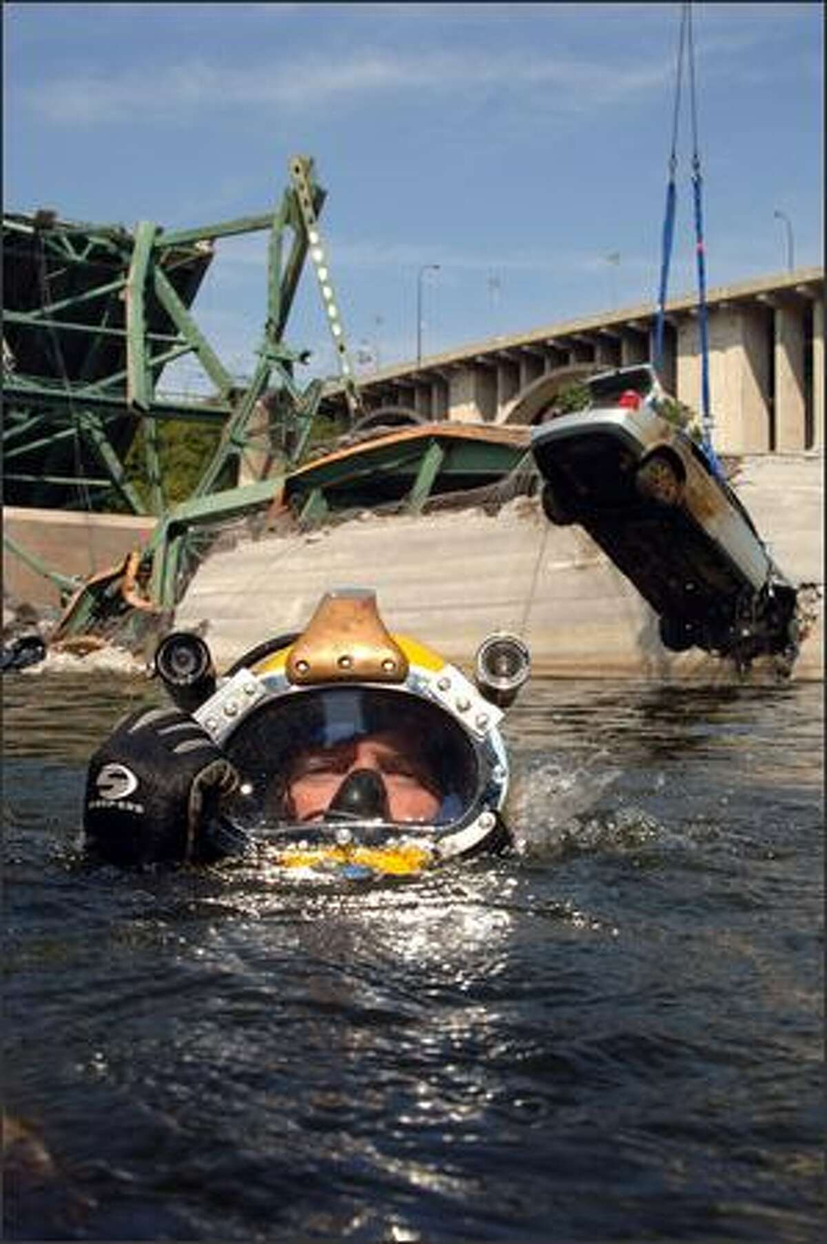 In this image made available on Thursday, Aug. 9, 2007, by the U.S. Navy, a Navy diver surfaces after completing a salvage dive in the Mississippi River, Wednesday, Aug. 8, 2007, as the vehicle he and his team rigged is lifted from the water in Minneapolis. Divers from the Navy and the FBI have joined local law enforcement divers in the effort to recover the people who remain missing and are presumed dead among the debris after the Interstate 35W bridge collapsed during the evening rush hour on Aug. 1. Photo/U.S. Navy, Andrew McKaskle