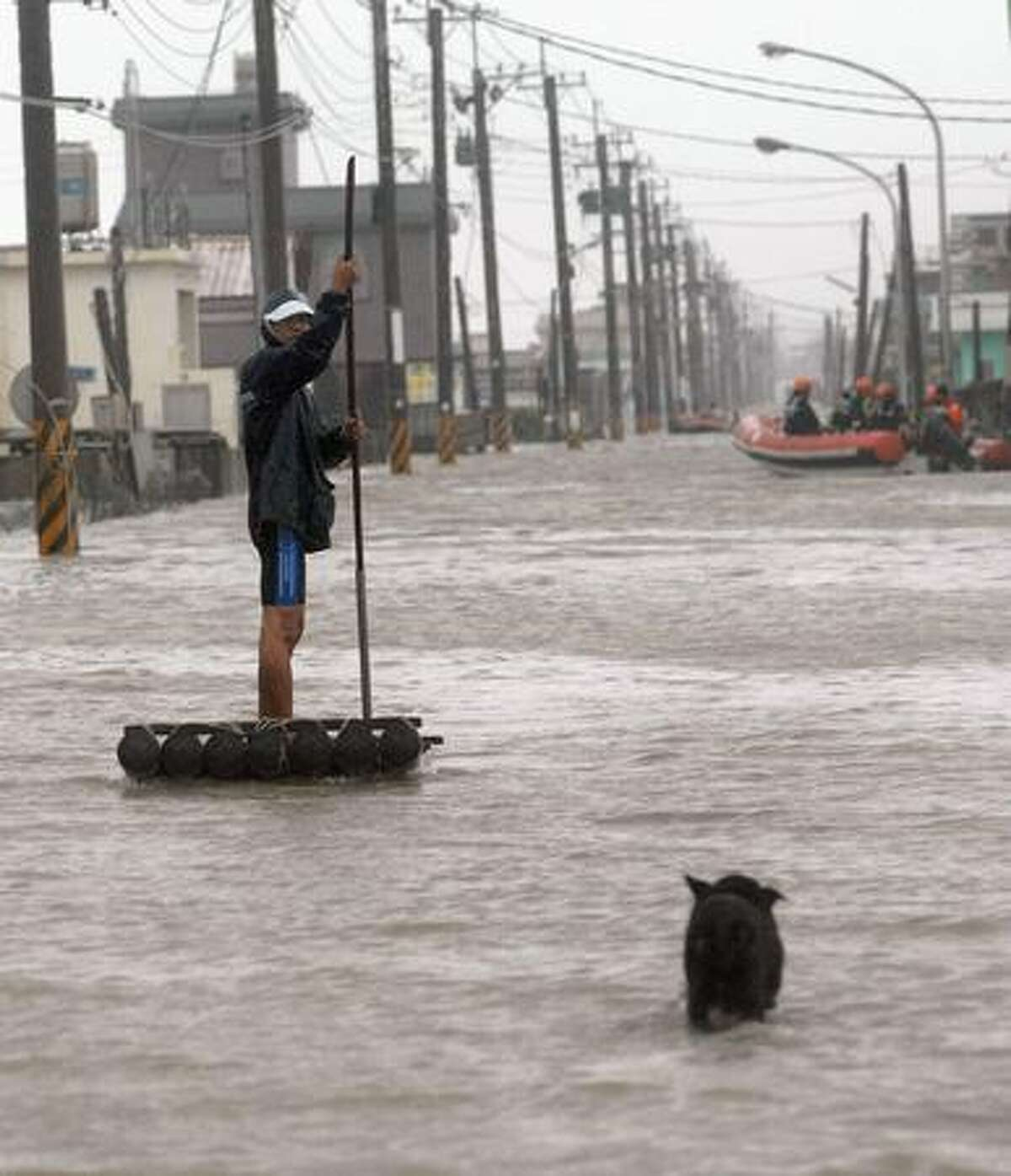 A man uses a makeshift raft to maneuver through the flooding brought by Typhoon Morakot in Chiatung, Pingtung county, in southern Taiwan, on Sunday. One person was killed and eight were missing and feared dead in Taiwan as Typhoon Morakot lashed the island with powerful winds and downpours, rescuers said on August 8.
