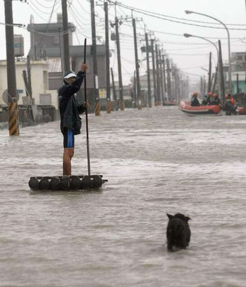 A man uses a makeshift raft to maneuver through the flooding brought by Typhoon Morakot in Chiatung, Pingtung county, in southern Taiwan, on Sunday. One person was killed and eight were missing and feared dead in Taiwan as Typhoon Morakot lashed the island with powerful winds and downpours, rescuers said on August 8. Photo: Getty Images / Getty Images