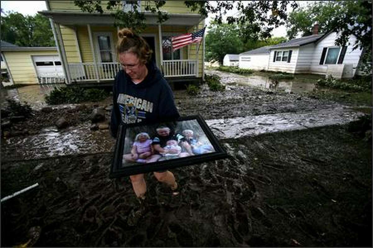 Karen Wilkemeyer carries a family photograph of her four children from her flooded home on Maple Street in Rushford Minn., on Monday, Aug. 20, 2007. Karen and her husband Tim Wilkemeyer stopped by their home Monday afternoon to see what they could save after Sunday morning heavy rain forced them from their home of 7 years. Photo/The Star Tribune, Jerry Holt