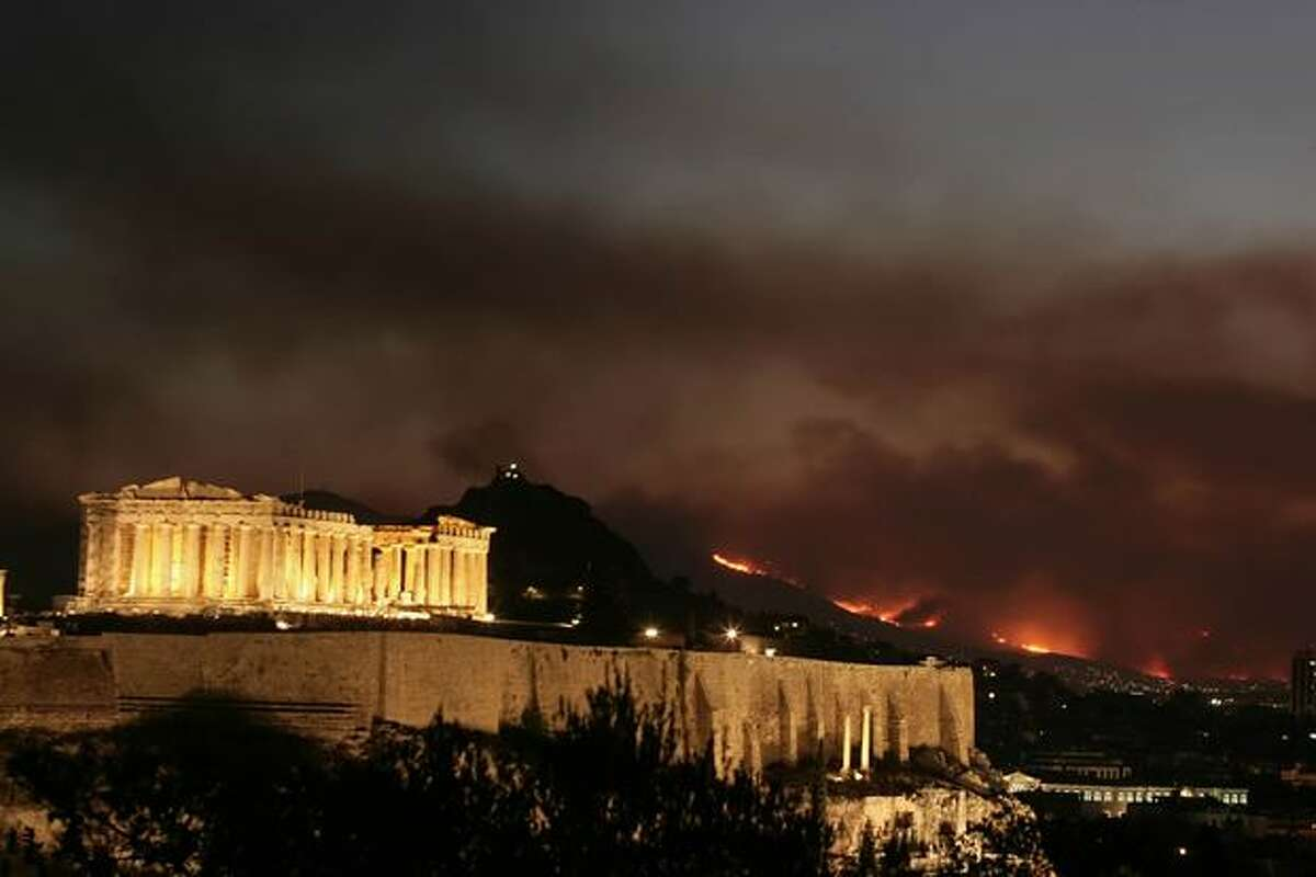 Wild fire and smoke illuminate the sky behind the ancient Acropolis on Sunday, in Athens, Greece. Authorities have declared a state of emergency as the large wildfire has raged since Friday, destroying homes and forcing thousands to flee the inferno. The blaze is the worst suffered by mainland Greece since 2007.