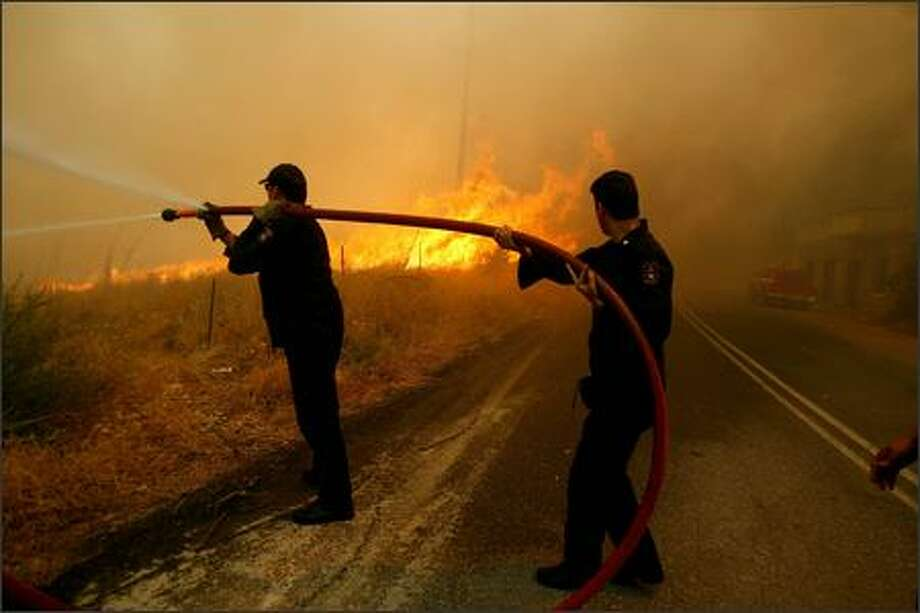 Firemen try to extinguish the fire that surrounded in the village of Kato Kotyli, central Peloponnese, about 250 kilometers southwest of Athens on Thursday, Aug. 30, 2007. Firefighters battled the country's last major blaze in southern Greece , after managing to bring under control hundreds of others that for one week ravaged large parts of the country and killed at least 64 people. AP Photo/Petros Giannakouris