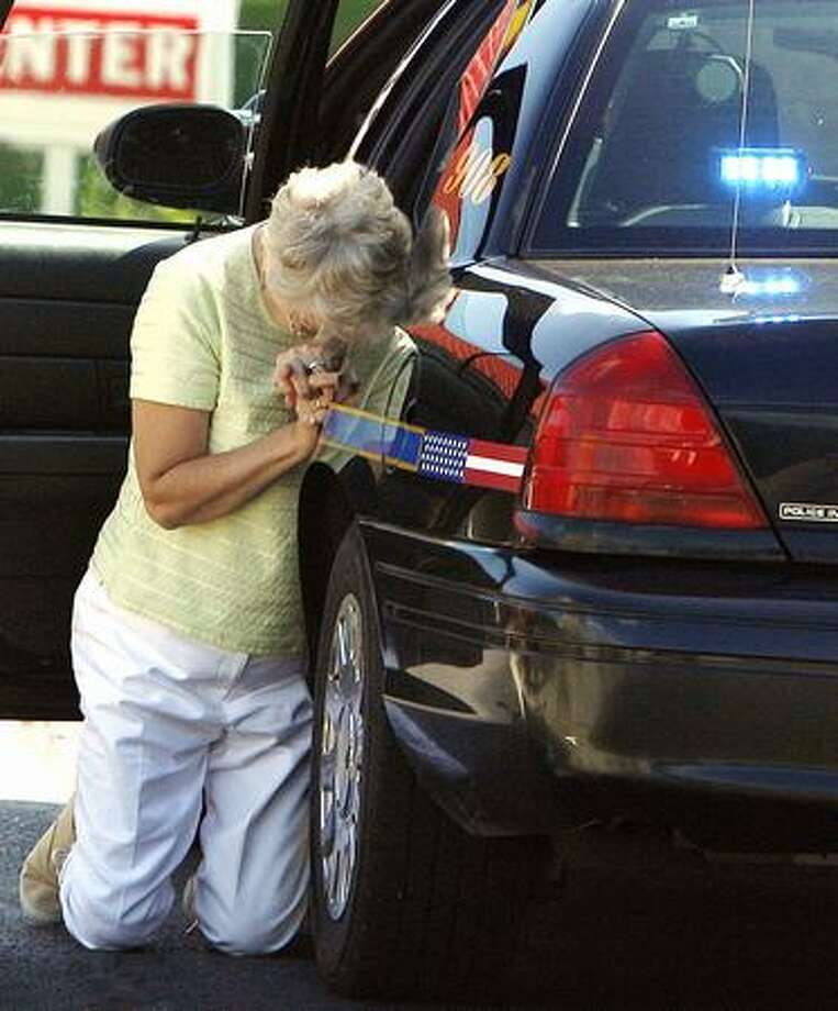 A woman kneels and prays next to a police car at the scene where a pedestrian was struck and killed Monday in Cold Spring, Ky. (AP Photo/The Enquirer, Patrick Reddy) Photo: AP Photo/WTJV-TV Via Miami Herald / AP Photo/WTJV-TV via Miami Herald