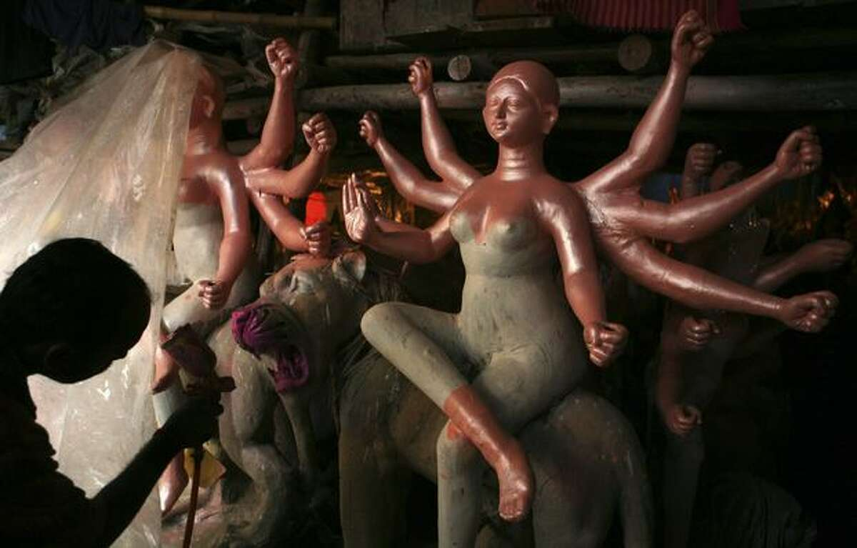 An artist gives final touches to an idol of Hindu goddess of valor, Durga, Monday for the forthcoming Durga festival in Allahabad, India. (AP Photo/Rajesh Kumar Singh)