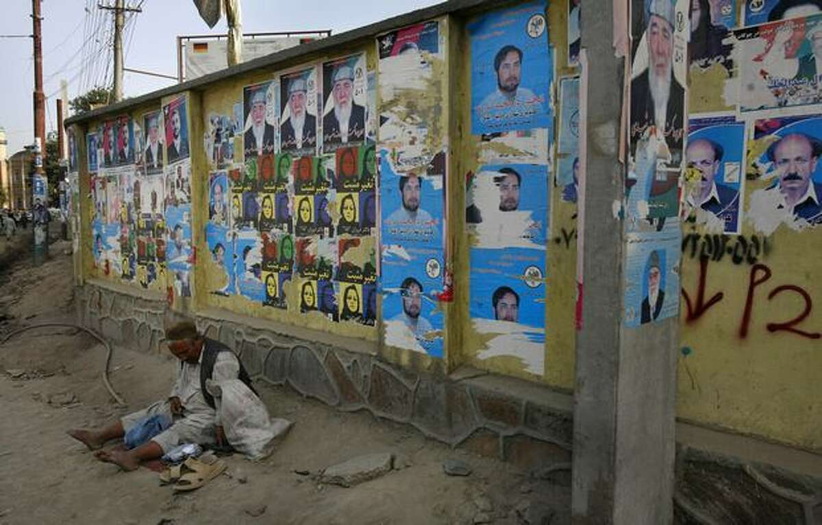 An Afghan beggar sits in front of a wall covered with election posters Monday in Kabul, Afghanistan. Various allegations of ballot box stuffing, voter intimidation and other election fraud have been lodged from many interested parties in Afghanistan, following last month's presidential election which reelected President Hamid Karzai, but an independent examination by The Associated Press, of the election ballot returns declared by the country's election commission, would appear to show some highly suspicious and improbable results.(AP Photo/Manish Swarup)
