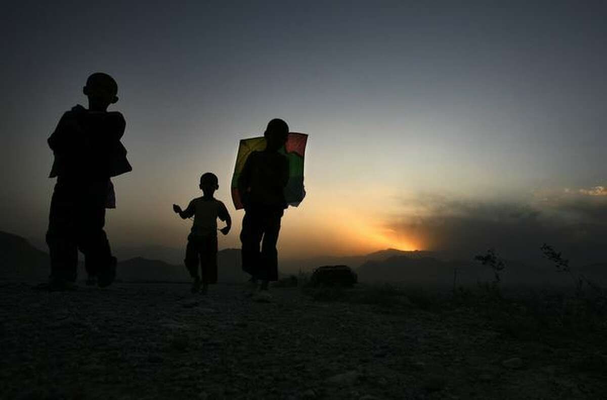 Afghan children return home Monday after a time flying their kite in Kabul, Afghanistan. (AP Photo/ Manish Swarup)