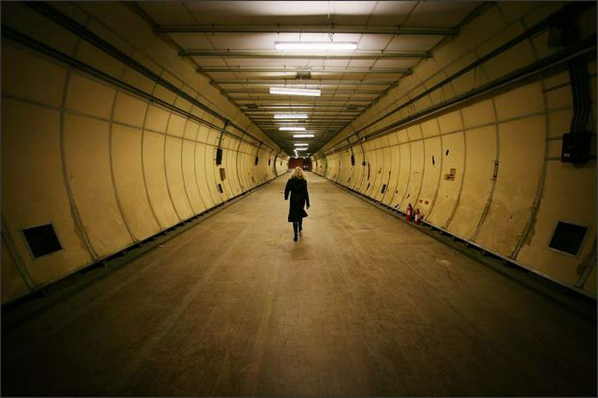 A visitor walks in a formely secret air raid tunnel called Third Avenue on October 17, 2008 in London. The once secret tunnels were built 100 feet under central London in 1940 as fully equipped air raid shelters and could accommodate 8000 people. They have since been used by MI6 and the Public Records Office to hold 400 tons of secret documents. Current owners British Telecom (BT) once housed the London trunk exchange of the secure Transatlantic hot line between the Presidents of the US and the Soviet Union. BT are now seeking a buyer as the tunnels are surplus to requirements.