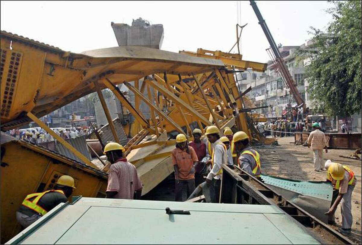 Workers gather at the site where a flyover bridge for the Delhi Metro collapsed in New Delhi on Sunday. At least two people were killed and 25 injured when a part of a metro flyover bridge that was under construction caved in at Shakarpur, near the Laximnagar area of East Delhi, crushing several passing vehicles including a blueline bus.