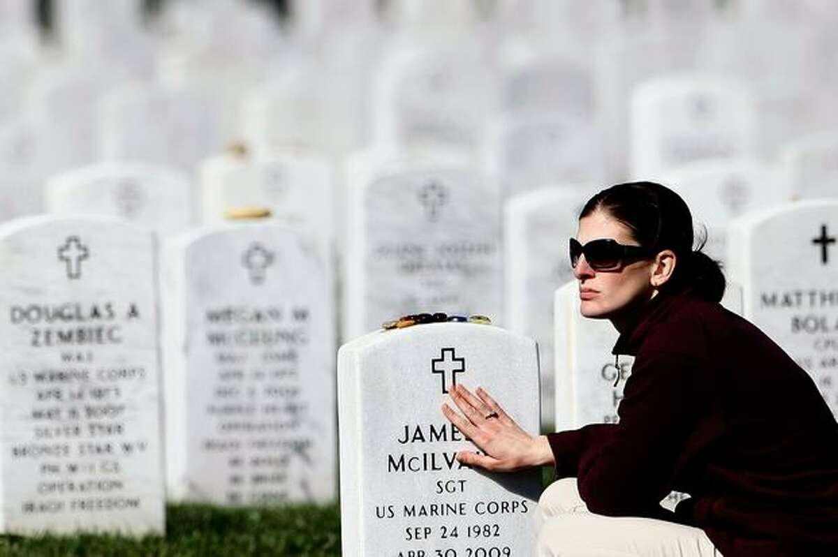Sheryl McIlvaine, widow of USMC Sgt. James McIlvaine, touches his gravestone while visiting Section 60 at Arlington National Cemetery during the burial service for Spc. Stephen Mace in Arlington, Va. McIlvaine and Mace were both from the Purcellville, Va., area. McIlvaine was killed in support of Operation Iraqi Freedom in April 2009, and Mace was killed October 3, 2009 along with seven other U.S. soldiers in the Nuristan province of Afghanistan.