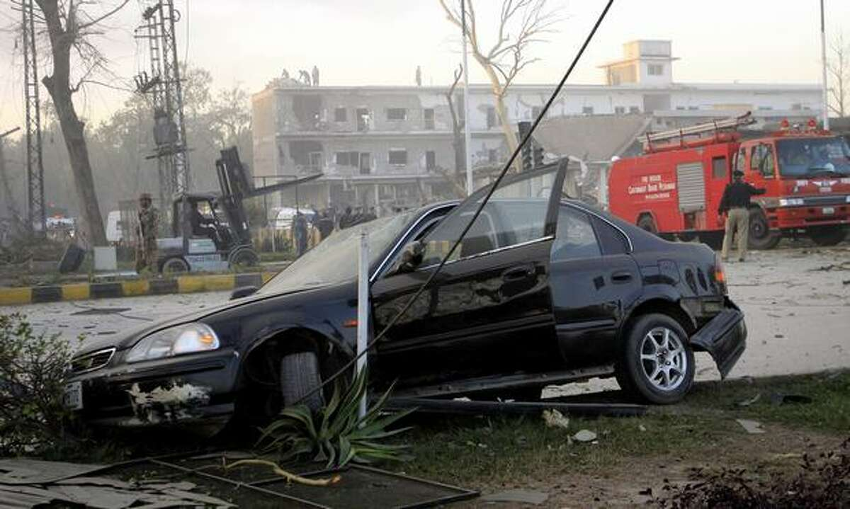 A destroyed car is seen after a suicide bombing in Peshawar, Pakistan on Friday. A suicide car bomb devastated Pakistan's main spy agency building in the northwest Friday, killing at least 7 people and striking at the heart of the institution overseeing much of the country's anti-terror campaign. (AP Photo/Mohammad Sajjad)