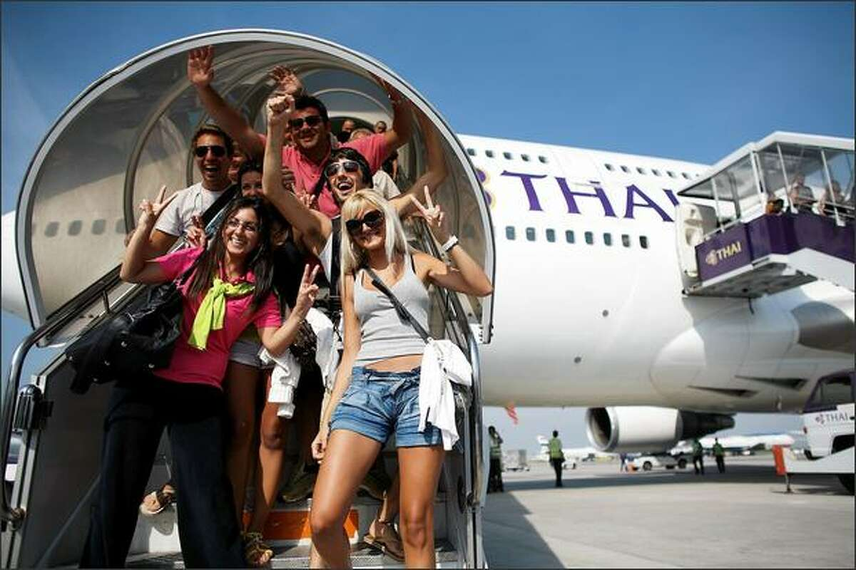 Passengers exit Thai Airways flight from Phuket, the first to arrive after the end of the seige, lands at Suvarnabhumi International Airport on Wednesday in Bangkok, Thailand. Yesterday, a court dissolved Thailand's top three ruling parties for electoral fraud, banned the prime minister from politics for five years and thus brought down a government that has faced months of protests. Deputy Prime Minister Chaowarat Chanveerakul will become the caretaker prime minister. The on-going political crisis during the holiday season stranded 300,000 foreign tourists, paralysing Thailand's lucrative tourist industry.