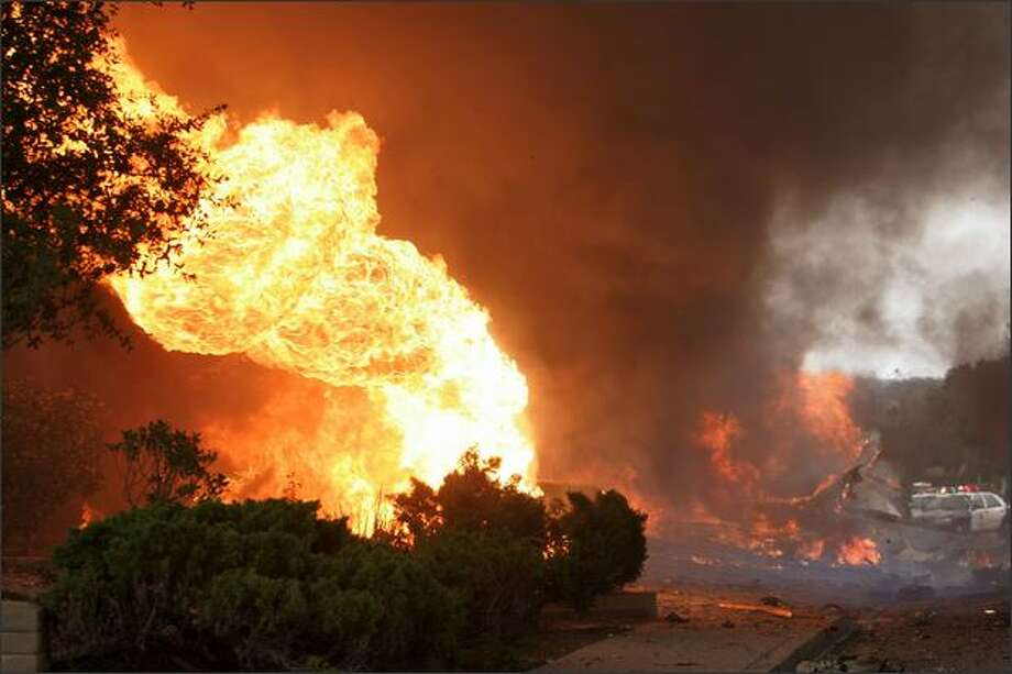 Fire rages in a neighborhood in the University City area Monday in San Diego, Calif. An FA-18 military jet crashed during a training exercise. The pilot ejected and suffered minor injuries. - Story: Military jet crash in San Diego kills 2 on ground Photo: Getty Images / Getty Images