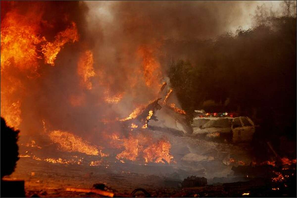 Fire rages in a neighborhood in the University City area Monday in San Diego, Calif. An FA-18 military jet crashed during a training exercise. The pilot ejected and suffered minor injuries. - Story: Military jet crash in San Diego kills 2 on ground