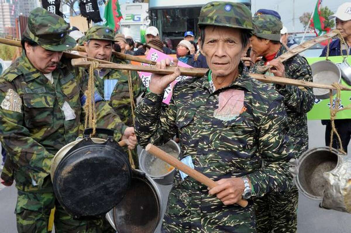 Taiwanese protesters wearing army-style camouflage uniforms carry pots during a demonstration in the island's central city of Taichung on Sunday against scheduled high-level talks between Taiwan and China on the island this week. Senior envoys from the two sides will meet in Taichung to discuss deceptively mundane issues like double taxation and agricultural quarantine.