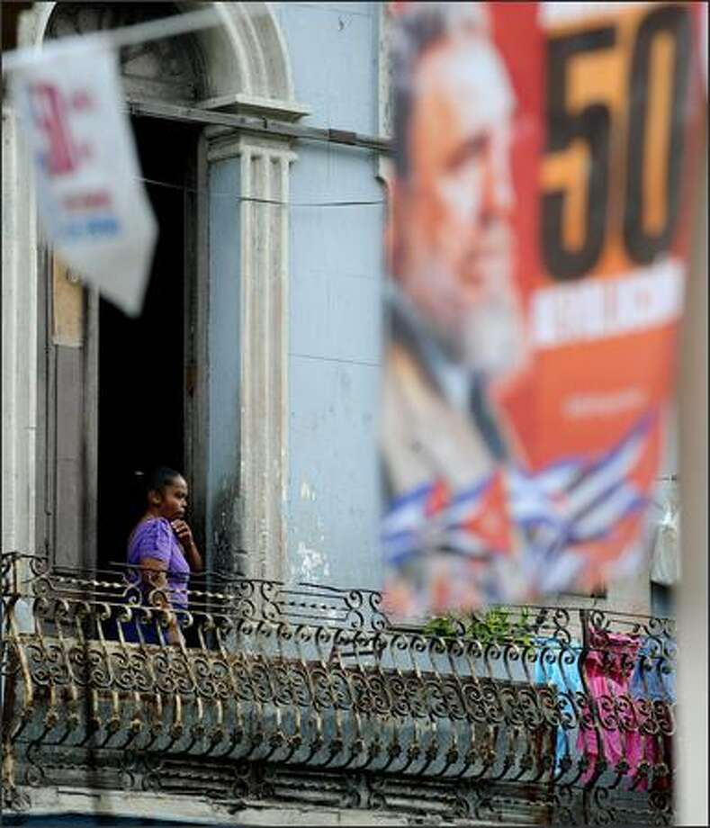 A women stays on a balcony in downtown Havana on Sunday. Next January 1st, 2009 marks the 50th anniversary of the Cuban Revolution, the date in which dictator Fulgencio Batista was forced to flee from Cuba by plane. Photo: Getty Images / Getty Images