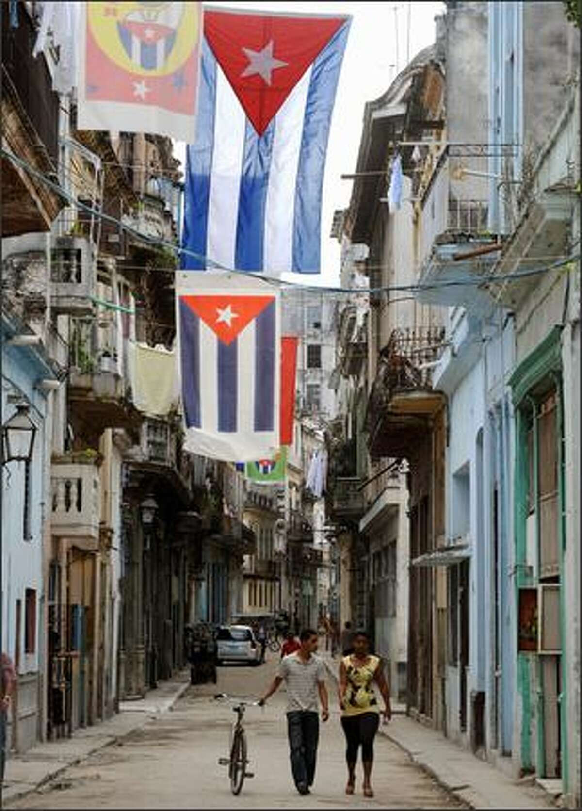 A couple strolls along a street decorated with Cuban flags in downtown Havana on Sunday. Next January 1st, 2009 marks the 50th anniversary of the Cuban Revolution, the date in which dictator Fulgencio Batista was forced to flee from Cuba by plane.