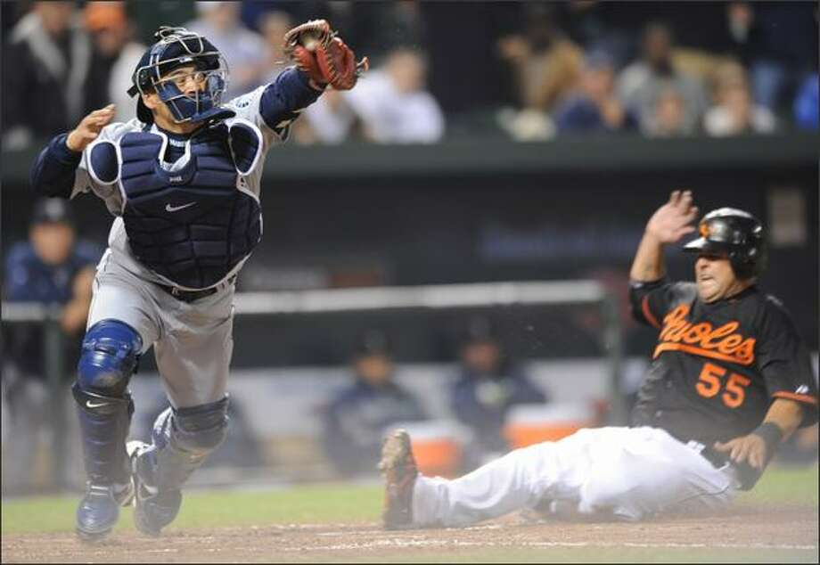 Baltimore Orioles' Ramon Hernandez, right, slides safely into home as Seattle Mariners catcher Kenji Johjima reaches for the throw during the fourth inning of a baseball game Friday, April 4, 2008 in Baltimore. Hernandez scored on a sarifice fly hit by Luis Hernandez.  (AP Photo/Gail Burton) Photo: Associated Press / Associated Press