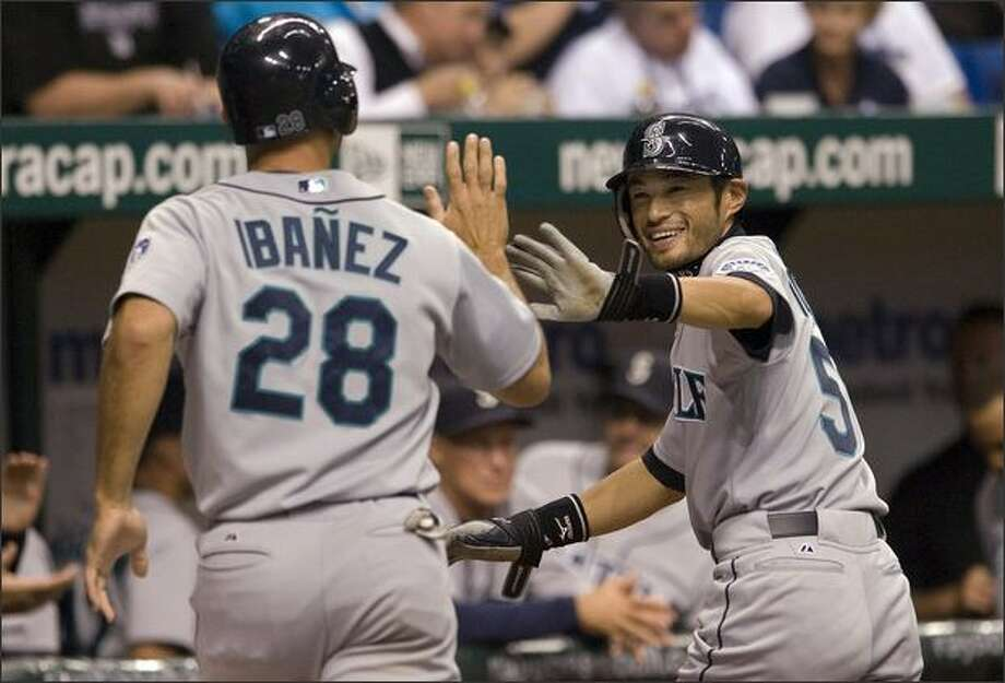 Seattle Mariners' Ichiro Suzuki, of Japan, right, congratulates Raul Ibanez (28) after they scored on a bases-loaded single by Brad Wilkerson off Tampa Bay Rays starter Matt Garza during the third inning of a baseball game Tuesday, April 8, 2008 in St. Petersburg, Fla. (AP Photo/Steve Nesius) Photo: Associated Press / Associated Press