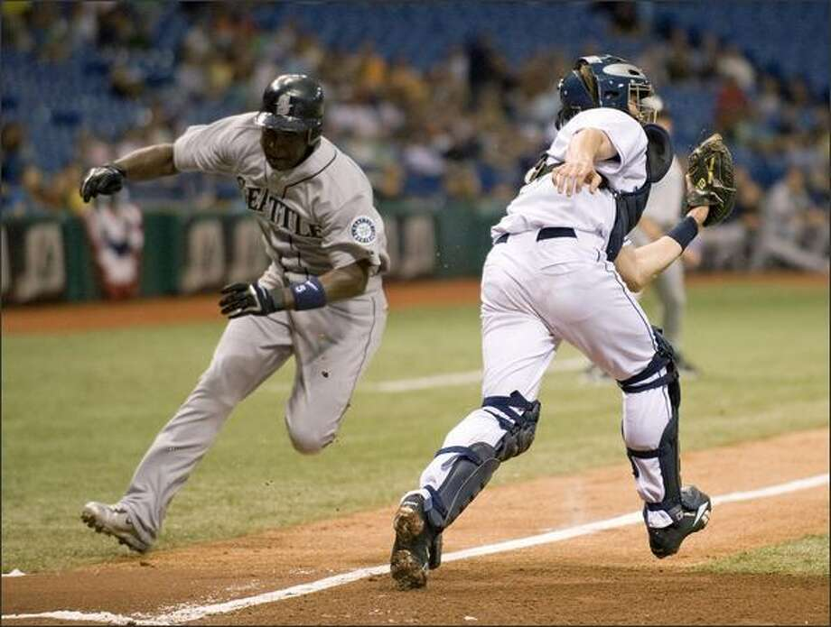 Tampa Bay Rays catcher Shawn Riggans, right, chases down a wide throw to the plate as Seattle Mariners Yuniesky Betancourt during the inning of a baseball game Wednesday, April 9, 2008 in St. Petersburg, Fla. (AP PhotoSteve Nesius) Photo: Associated Press / Associated Press