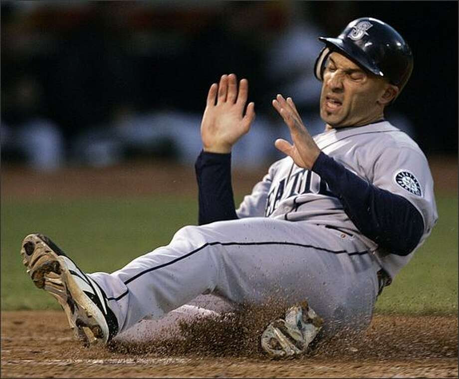 Seattle Mariners' Raul Ibanez slides to score against the Oakland Athletics during the third inning of a baseball game Wednesday, April 16, 2008, in Oakland, Calif. Ibanez scored on a triple by Adrian Beltre. (AP Photo/Ben Margot) Photo: Associated Press / Associated Press
