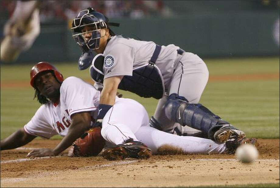 Los Angeles Angels' Vladimir Guerrero, left, scores after Seattle Mariner' catcher Kenji Johjima of Japan, looses the ball in the first inning during their MLB baseball game, Friday, April 18, 2008 in Anaheim, Calif. (AP Photo/Gus Ruelas) Photo: Associated Press / Associated Press