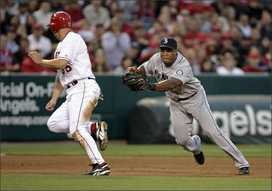 Mariners shortstop Yuniesky Betancourt, right, tries unsuccessfully to keep Los Angeles' Rob Quinlan from advancing to third base in the fourth inning. (AP Photo/Mark Avery) Photo: Associated Press / Associated Press