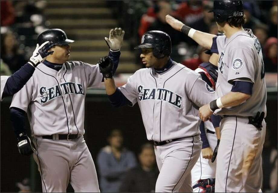 Wladimir Balentien, center, is congratulated by teammates Jose Vidro, left, and Richie Sexson after hitting a three-run home run off Cleveland pitcher Cliff Lee in the seventh inning. Photo: Associated Press / Associated Press