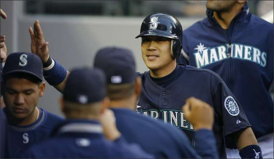 Seattle's Kenji Johjima is congratulated after scoring on a Jose Lopez single to center in the second inning against the Texas Rangers at Safeco Field. Photo: Gilbert W. Arias, Seattle Post-Intelligencer / Seattle Post-Intelligencer